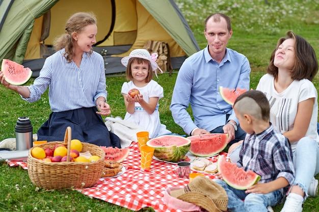 Szczęśliwy Rodzinny łasowanie Arbuz Przy Pinkinem W łące Blisko Namiotu. Rodzina Spożywająca Wakacje Na Kempingu Na Wsi Premium Zdjęcia