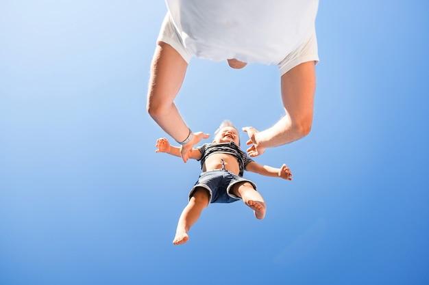 Szczęśliwy Rodzinny Ojciec I Syn. Tata Rzuca Dziecko Wysoko Ponad Siebie Premium Zdjęcia