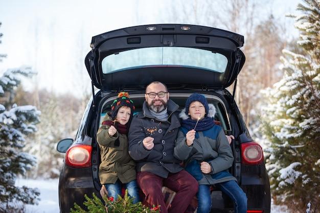 Szczęśliwy Rodzinny Pobliski Czarny Samochód Przy śnieżnym Zima Dniem. Wakacje Urlopowe. Premium Zdjęcia