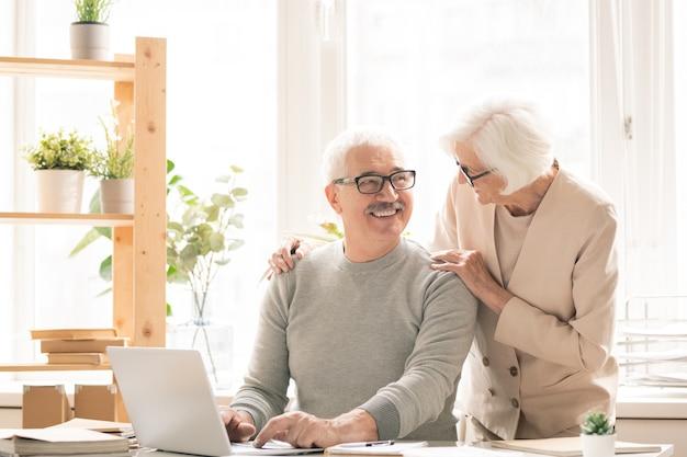 Szczęśliwy Starszy Mężczyzna W Casualwear Siedzi Przy Biurku Przed Laptopem, Rozmawiając Z żoną Stojącą Przy Nim Premium Zdjęcia