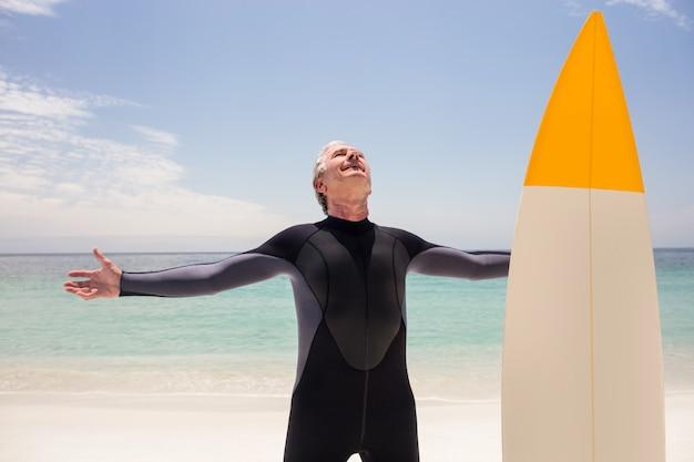 Szczęśliwy starszy mężczyzna w kombinezon stojący z rozpostartymi ramionami Premium Zdjęcia