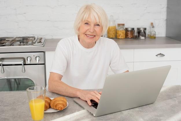 Szczęśliwy starszy obsiadanie w kuchni z laptopem Darmowe Zdjęcia