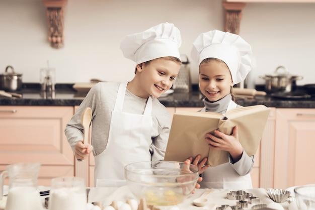 Szczęśliwy Syn I Córka Gotują Z Książką Kucharską. Premium Zdjęcia