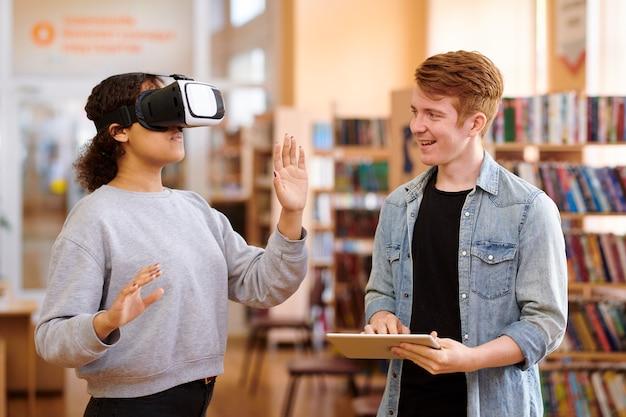 Szczęśliwy Uczeń Korzystający Z Tabletu Podczas Interakcji Ze Swoim Kolegą Z Klasy Za Pomocą Zestawu Słuchawkowego Vr W Bibliotece Premium Zdjęcia