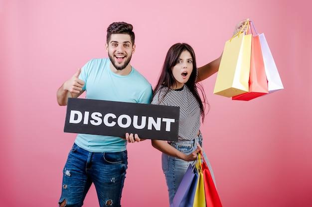 Szczęśliwy uśmiechający się przystojny para mężczyzna i kobieta ze znakiem zniżki i kolorowe torby na zakupy Premium Zdjęcia