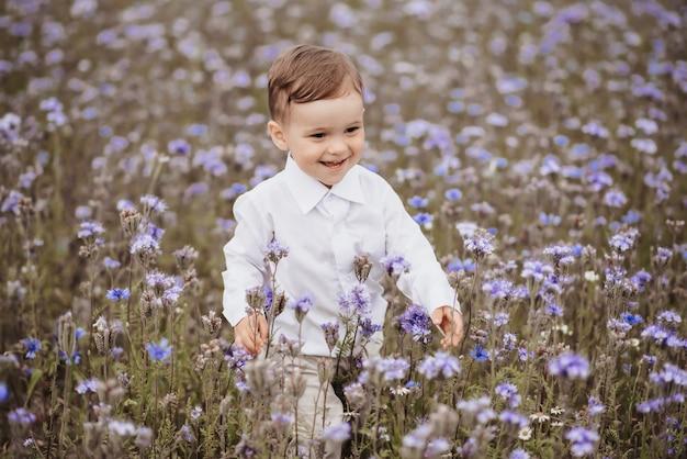 Szczęśliwy Uśmiechnięty Chłopiec świetnie Się Bawi W Dziedzinie Kwiatów Premium Zdjęcia