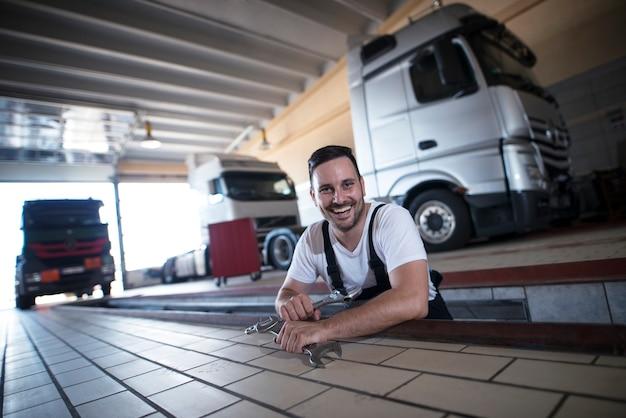 Szczęśliwy Uśmiechnięty Mechaników Pojazdów Posiadających Narzędzia Klucza W Warsztacie Naprawy Ciężarówek Darmowe Zdjęcia
