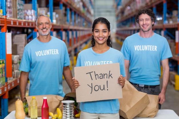 Szczęśliwy Wolontariusz Trzyma Znak I Pozuje Z Jej Drużyną Premium Zdjęcia