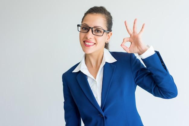 Szczęśliwy Z Podnieceniem Młody Bizneswoman W Eyeglasses Pokazuje Ok Znaka. Darmowe Zdjęcia