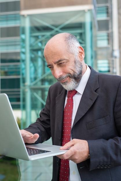 Szczęśliwy Zadowolony Dojrzały Biznesmen Z Laptopu Dopatrywania Zawartością Darmowe Zdjęcia