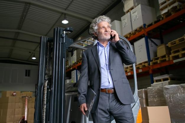 Szczęśliwy Zamyślony Biznesmen Stojący W Pobliżu Wózka Widłowego W Magazynie I Rozmawia Przez Telefon Komórkowy. Półki Z Towarami W Tle. Koncepcja Biznesowa Lub Logistyczna Darmowe Zdjęcia