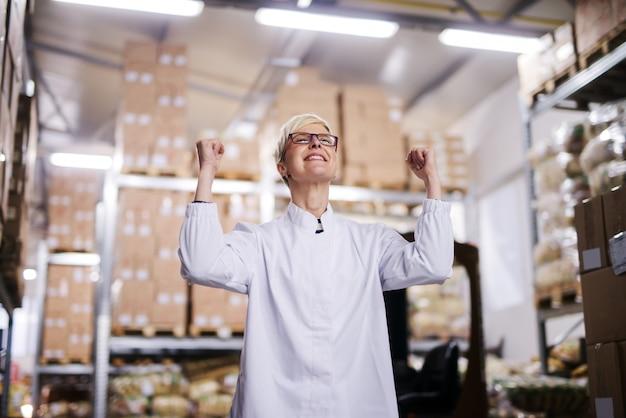 Szczęśliwy żeński Pracownik Fabryczny świętuje Sukces. Wnętrze Magazynu Premium Zdjęcia