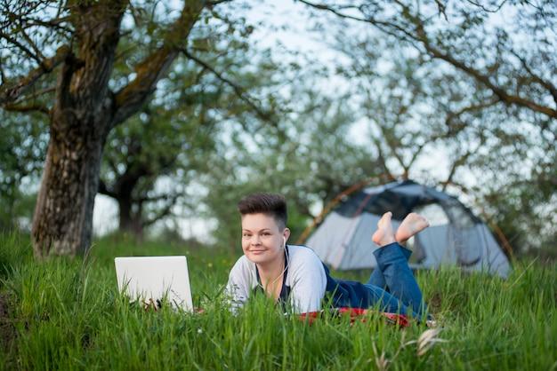 Szczęśliwy żeński Relaksować Na Trawie Używać Jej Laptop Podczas Gdy Obozujący W Lesie Premium Zdjęcia
