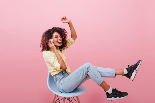 Szczupła Afrykańska Kobieta Z Długimi Nogami, Słuchanie Muzyki I śmiejąc Się. Oszałamiająca Mulat Modelka W Czarnych Butach Siedzi Na Niebieskim Krześle. Darmowe Zdjęcia