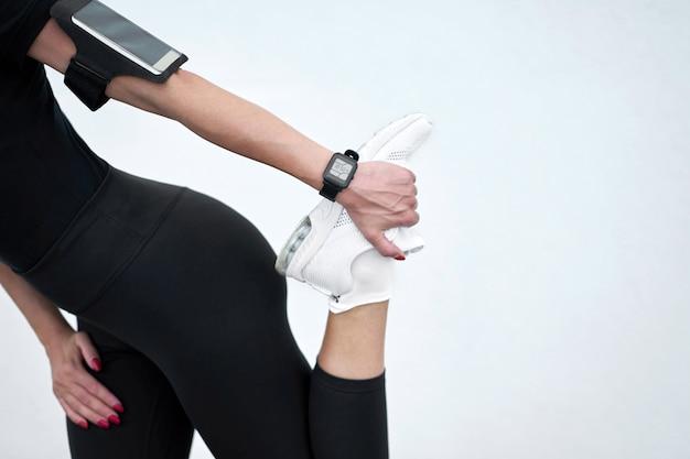 Szczupła dziewczyna jest ubranym czarnego sportswear rozciąganie na biel ściany tle Premium Zdjęcia