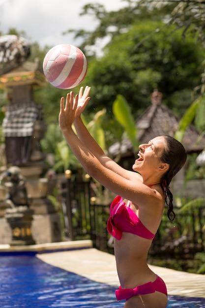 Szczupła Dziewczyna W Seksownym Różowym Stroju Kąpielowym Gra W Piłkę W Tropikalnym Basenie W Dżungli Premium Zdjęcia