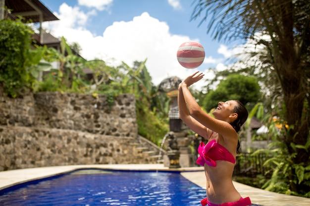 Szczupła Dziewczyna W Seksownym Różowym Stroju Kąpielowym Gra W Piłkę W Tropikalnym Basenie Premium Zdjęcia