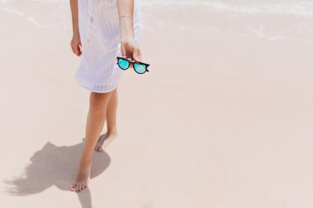 Szczupła Kobieta Pozuje Na Wybrzeżu Z Okularami Przeciwsłonecznymi. Odkryty Strzał Zrelaksowanej Kobiety Boso W Białej Sukni Stojącej W Pobliżu Oceanu. Darmowe Zdjęcia
