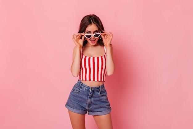 Szczupła Kobieta W Dżinsowych Szortach I Topie W Paski Zakłada Stylowe Okulary Przeciwsłoneczne Na Różowej ścianie Darmowe Zdjęcia