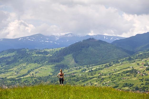 Szczupła młoda kobieta stojąca na trawiastej dolinie na tle zielonych gór w słoneczny letni dzień Premium Zdjęcia