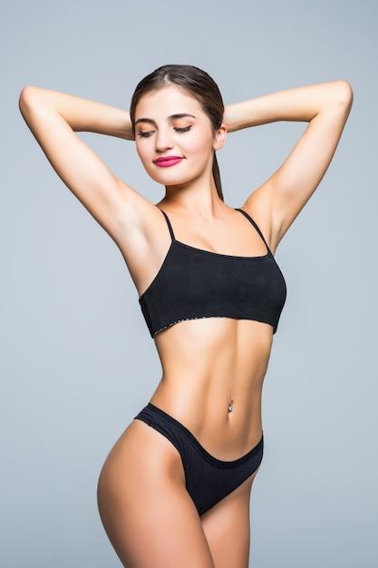 Szczupłe Ciało Młodej Kobiety W Czarnym Bikini. Dziewczyna Z Zdrowy Sportowy Rysunek Na Białej ścianie Darmowe Zdjęcia