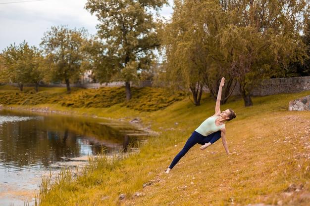 Szczupły młody jogin brunetka wykonuje trudne ćwiczenia jogi na żółtej trawie jesienią wbrew naturze Premium Zdjęcia