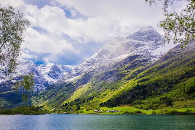 Szczyty Górskie W śniegu. Malowniczy Krajobraz. Fiord W Norwegii. Naturalna Tapeta. Górski Krajobraz Skandynawski. Tło Wiosna Premium Zdjęcia