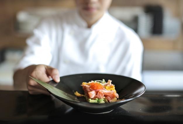 Szef Kuchni Przedstawia Tatar Z Ryby W Czarnej Płycie Premium Zdjęcia