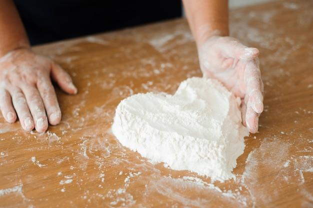 Szef kuchni przygotowuje ciasto - proces gotowania, serce mąki. Premium Zdjęcia