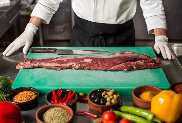 Szef kuchni stoi w kuchni, aby przygotować stek wołowy Darmowe Zdjęcia