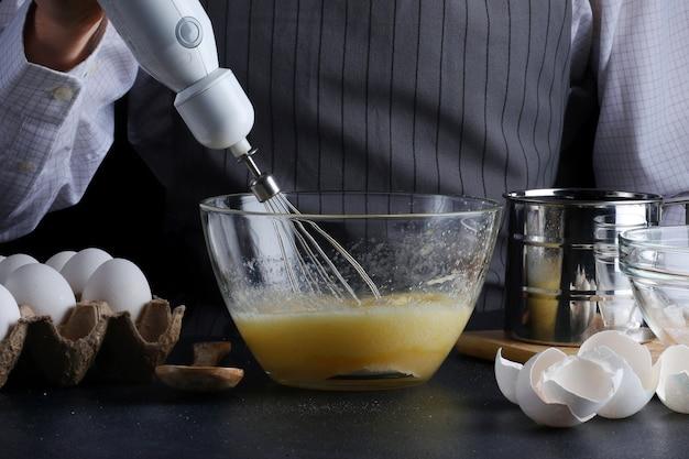 Szef Kuchni Z Mikserem W Rękach Gotowanie Ciasta Ze Składnikami Na Stole Premium Zdjęcia