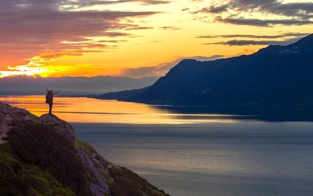 Szeroka Panorama Górskiego Jeziora. Mała Sylwetka Turysty Z Plecakiem Na Skalistym Zboczu Góry Z Uniesionymi Rękami Na Wodzie Jeziora Pokryte Premium Zdjęcia