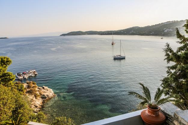 Szeroki Strzał łodzie Na Zbiorniku Wodnym Otaczającym Górami I Zielonymi Roślinami W Skiathos, Grecja Darmowe Zdjęcia