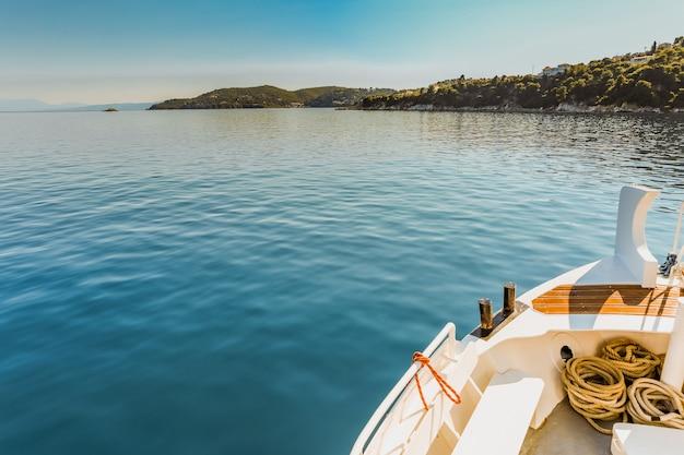 Szerokie Ujęcie Białego Czółna Na Zbiorniku Wodnym W Pobliżu Zielonej Wyspy Pod Jasnym Błękitnym Niebem Darmowe Zdjęcia
