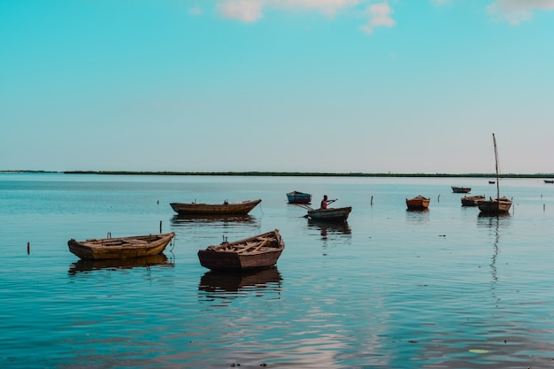 Szerokie Ujęcie Drewnianych Małych łodzi W Wodzie Z Afroamerykańską Osobą W Jednej Z Nich Darmowe Zdjęcia
