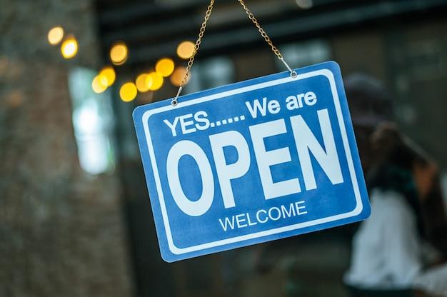 Szeroko otwarty znak przez szybę w kawiarni Darmowe Zdjęcia
