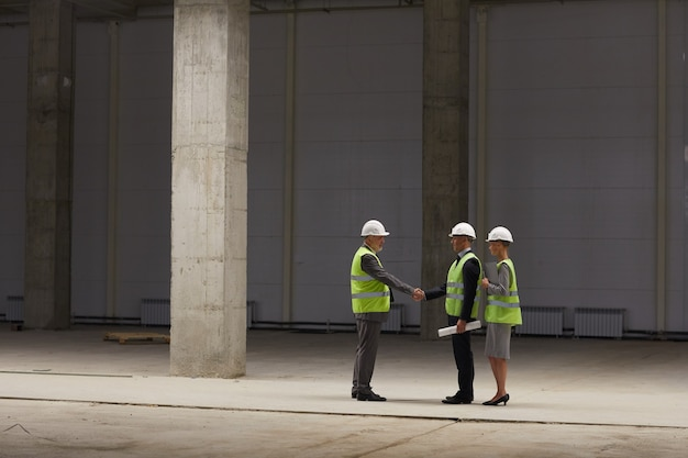 Szerokokątny Portret Ludzi Biznesu ściskających Ręce Podczas Omawiania Transakcji Inwestycyjnej Na Placu Budowy W Pomieszczeniach, Premium Zdjęcia