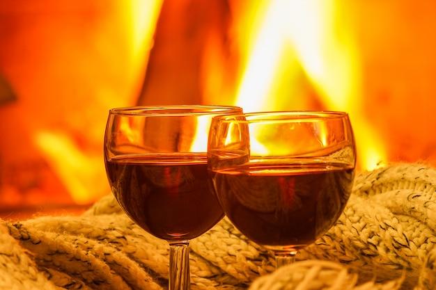 Szkła czerwone wino przeciw wygodnemu kominkowemu tłu, zbliżenie, zima wakacje. Premium Zdjęcia