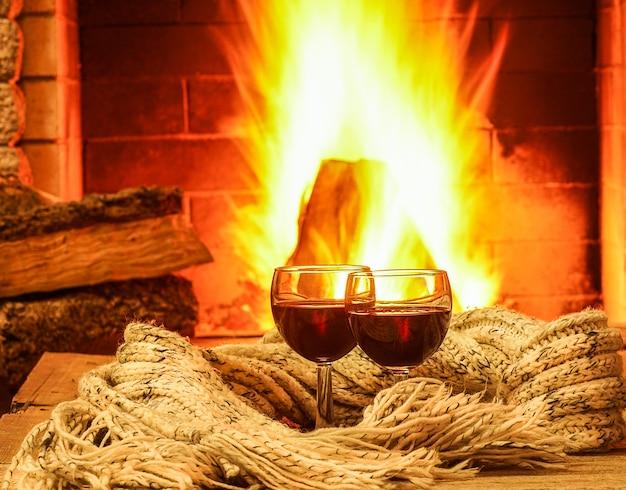 Szkła czerwone wino przeciw wygodnemu kominkowemu tłu, zima wakacje. Premium Zdjęcia