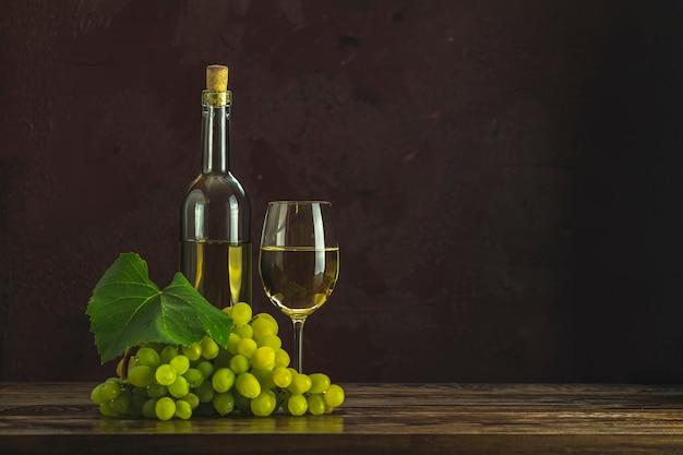 Szkła I Butelki Biały Wino I Winogrona Na Ciemnym Claret Bordach Betonują Nawierzchniowego Tło Premium Zdjęcia