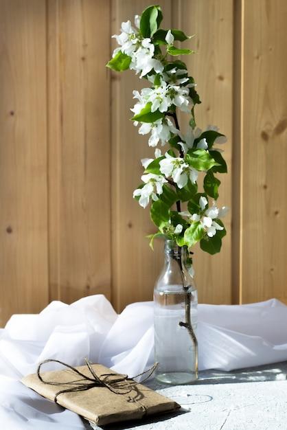 Szklana Butelka Z Kwitnących Gałęzi Wiśni, Jabłoń Na Drewnianym Tle. Kompozycja Kwiatowa W Słoneczny Dzień Wiosny. Premium Zdjęcia
