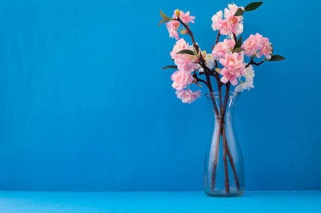 Szklana Waza Z Różowym Kwiatem Sakury Na Niebieskim Tle Premium Zdjęcia