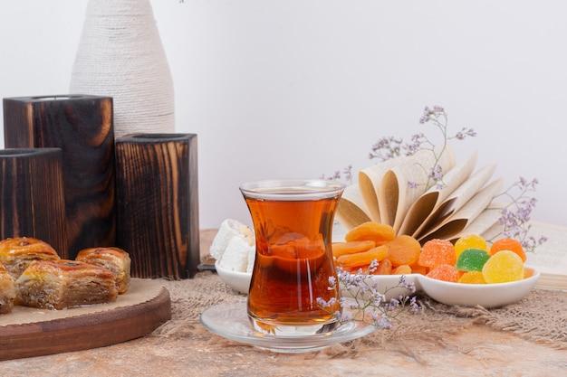 Szklanka Herbaty, Różne Słodycze I Suszone Morele Na Marmurowym Stole. Darmowe Zdjęcia