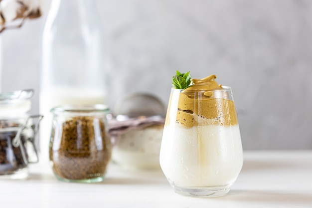 Szklanka Kawy Mrożonej Dalgona, Modnej Puszystej Kremowej Bitej Kawy, Ozdobionej Miętą Premium Zdjęcia