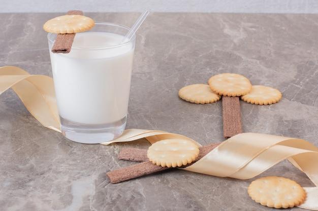 Szklanka Mleka Z Ciastkami I Wstążką Na Marmurowym Stole. Darmowe Zdjęcia