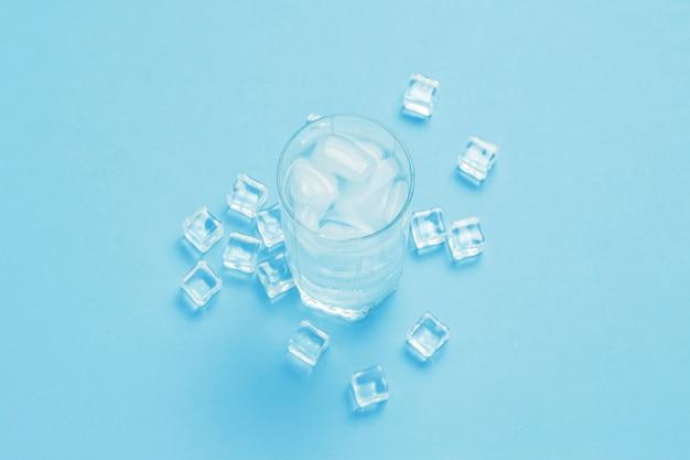 Szklanka Orzeźwiającej Zimnej Wody Z Lodem I Kostkami Lodu Na Niebieskiej Powierzchni. Premium Zdjęcia
