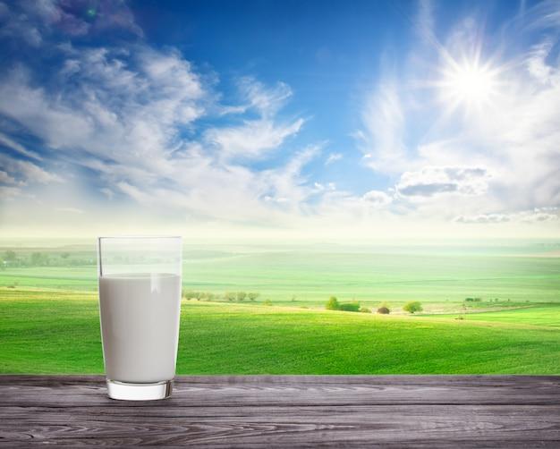 Szklanka świeżego Mleka Na Falistym Zielonym Pastwisku Premium Zdjęcia