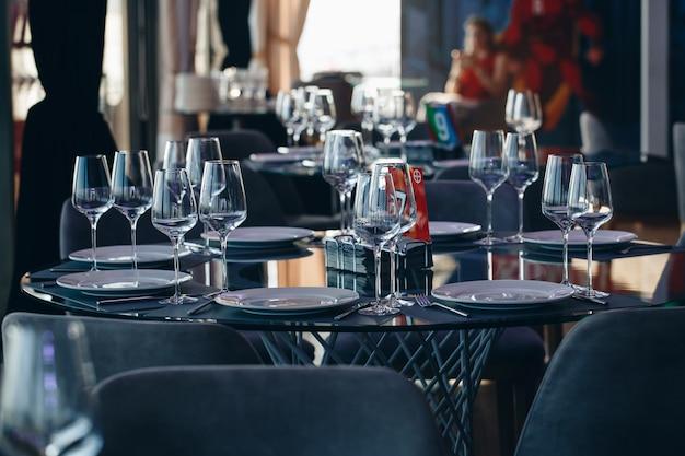 Szklanki, Widelec Do Kwiatów, Nóż Podawane Na Obiad W Restauracji Z Przytulnym Wnętrzem Premium Zdjęcia