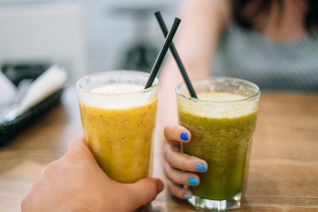 Szklanki Z Smoothie Warzywno-owocowym. Mężczyzna I Kobieta Trzymając Okulary Ze Szpinakiem I Smoothie Premium Zdjęcia