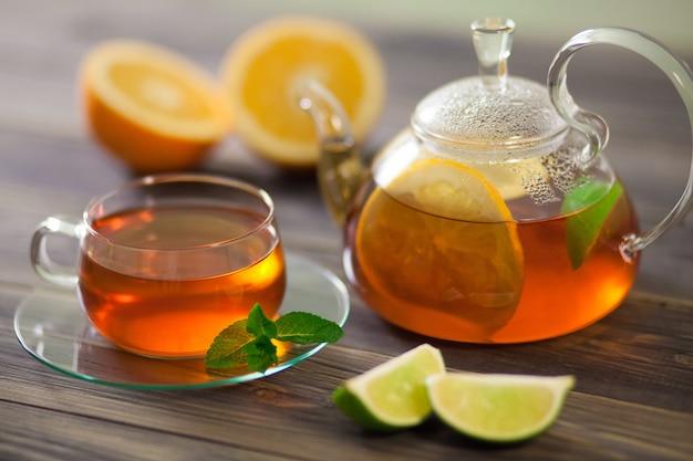 Szklany czajniczek i filiżanka czarnej herbaty z pomarańczą, cytryną, miętą limonki na drewnianym stole Premium Zdjęcia